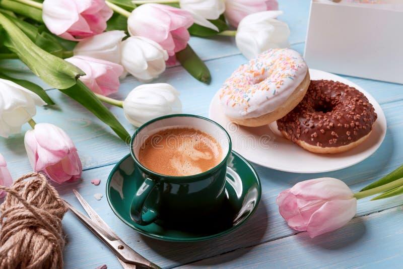 Donuts, kawa i tulipany na błękitnym drewnianym tle, obraz stock