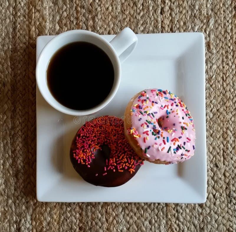 Donuts med koppen av svart kaffe arkivfoto