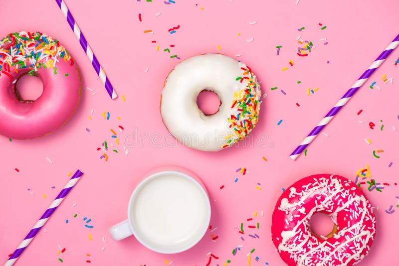 Donuts met suikerglazuur en melk op pastelkleur roze achtergrond Zoete donu stock foto's