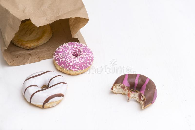 Donuts met wit, roze en chocoladesuikerglazuur, 3 donuts, 1 gebeten doughnut stock afbeeldingen