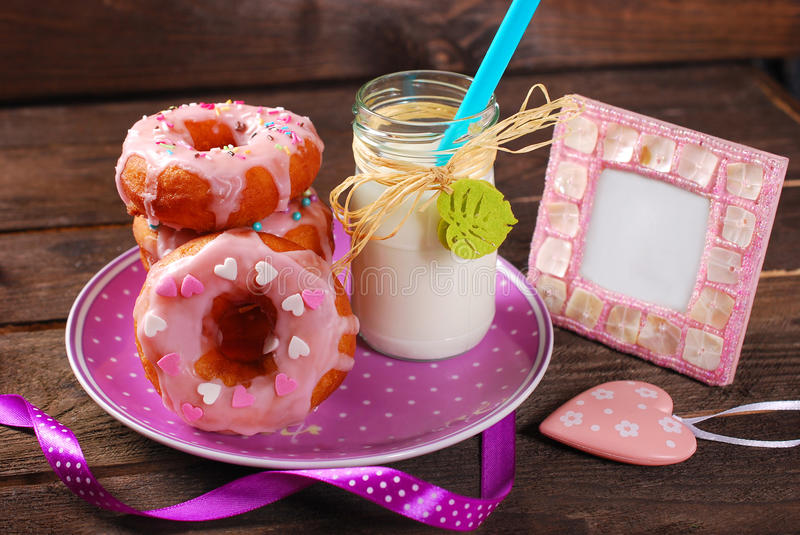 Donuts and milk. Homemade donuts with pink icing and sprinkles on plate and bottle of milk stock images