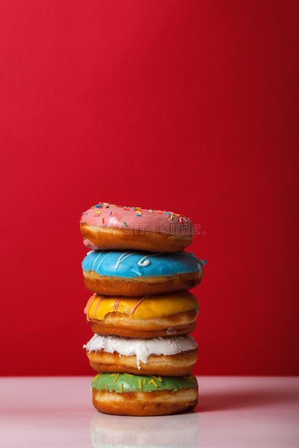 Donuts in multi-colored glans bovenop elkaar op een rode achtergrond wordt gestapeld, exemplaarruimte die Bakkerij reclameconcept royalty-vrije stock foto's