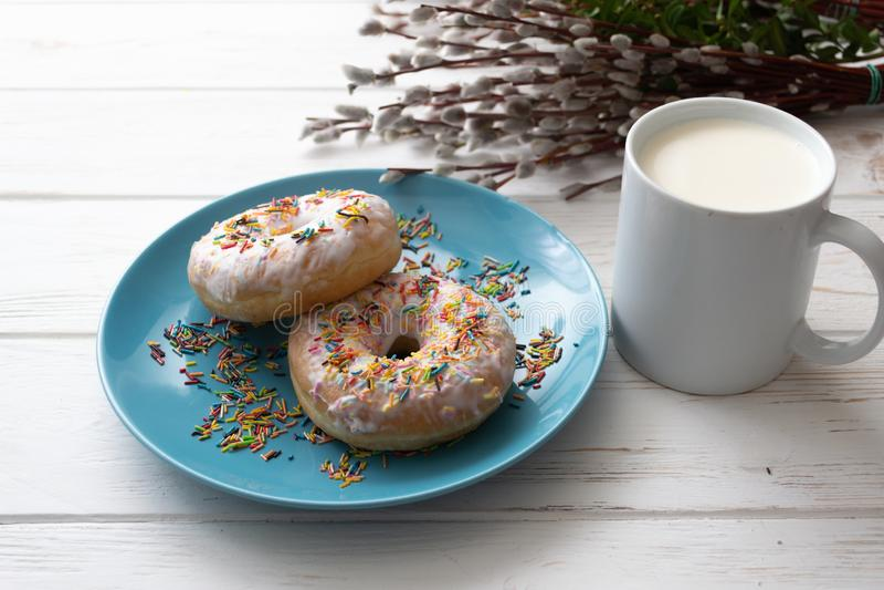 Donuts na błękitnym talerzu z filiżanką mleko na białym drewnianym tle obraz royalty free