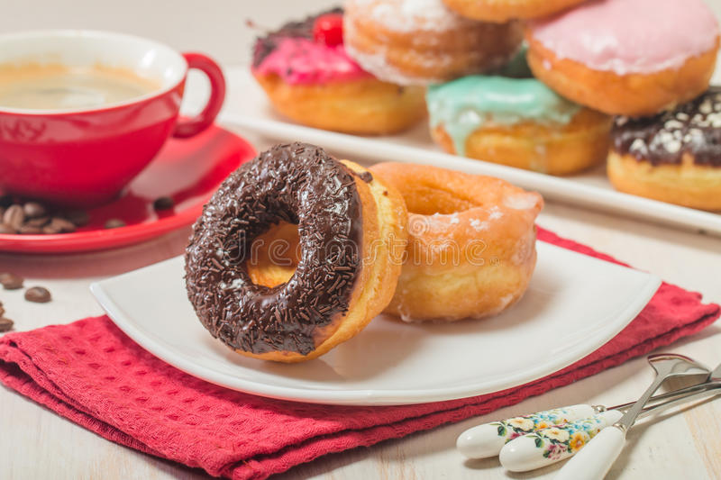 Donuts on a plate and coffee. On white wooden background royalty free stock photo