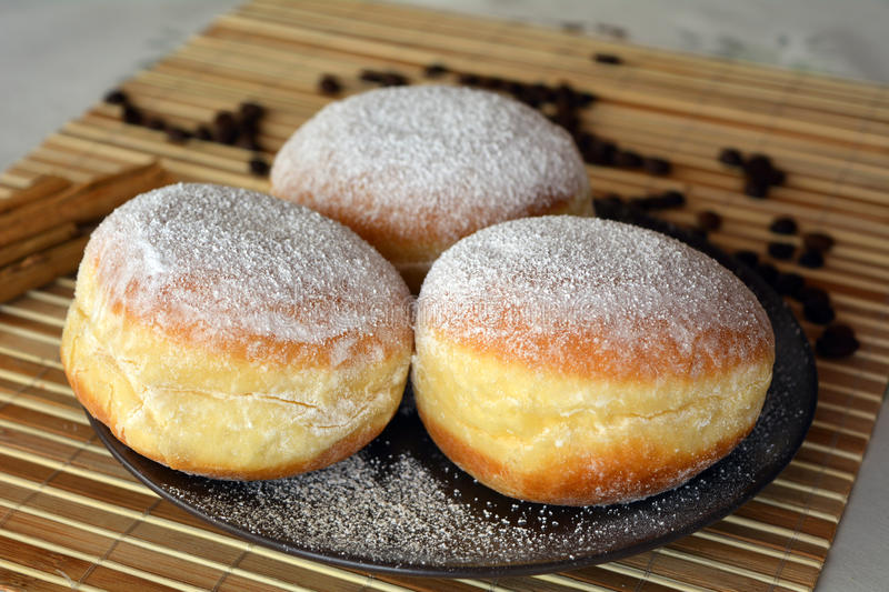 Donuts with powdered sugar on the brown plate on the table stock photography
