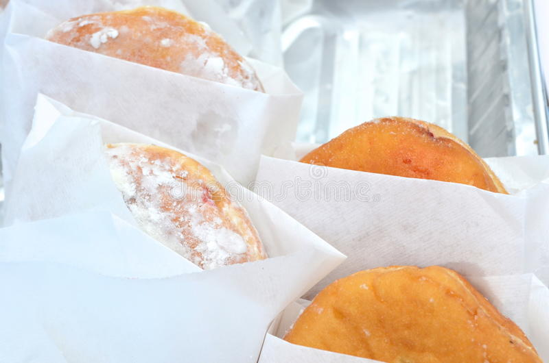 Donuts. Powdered sugar and jelly donuts peeking out of white paper wrappers royalty free stock images