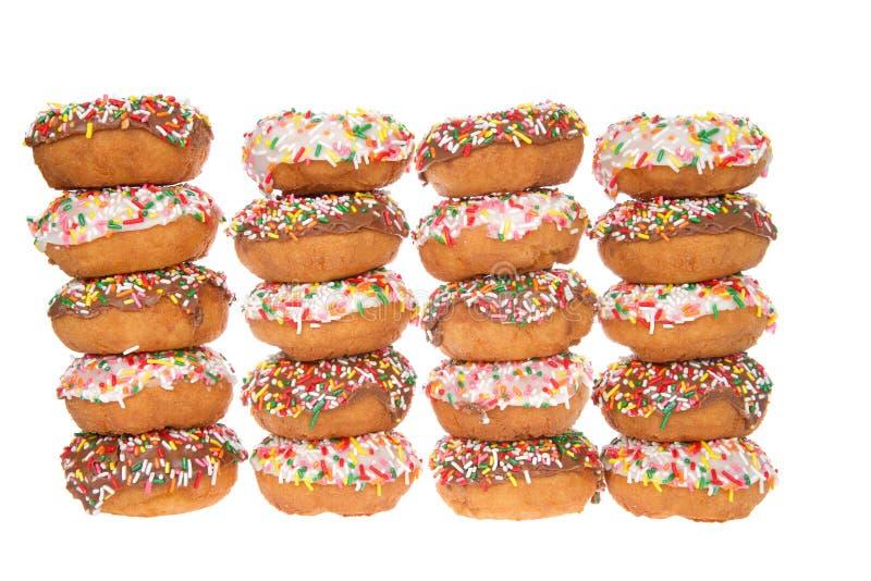 Donuts in rijen wordt die die chocolade en vanille afwisselen op wit wordt geïsoleerd gestapeld dat stock foto's