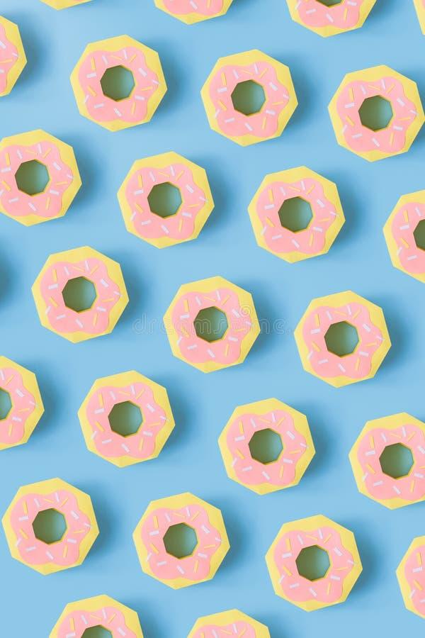 Donuts robić papieru wzór na błękitnym pastelowym tle ilustracja wektor