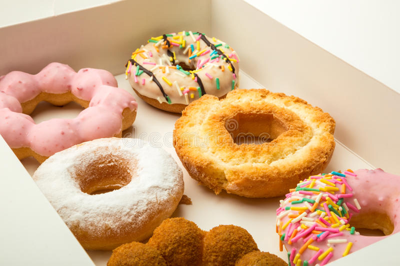 Donuts. Six colorful assorted donuts in a box royalty free stock images
