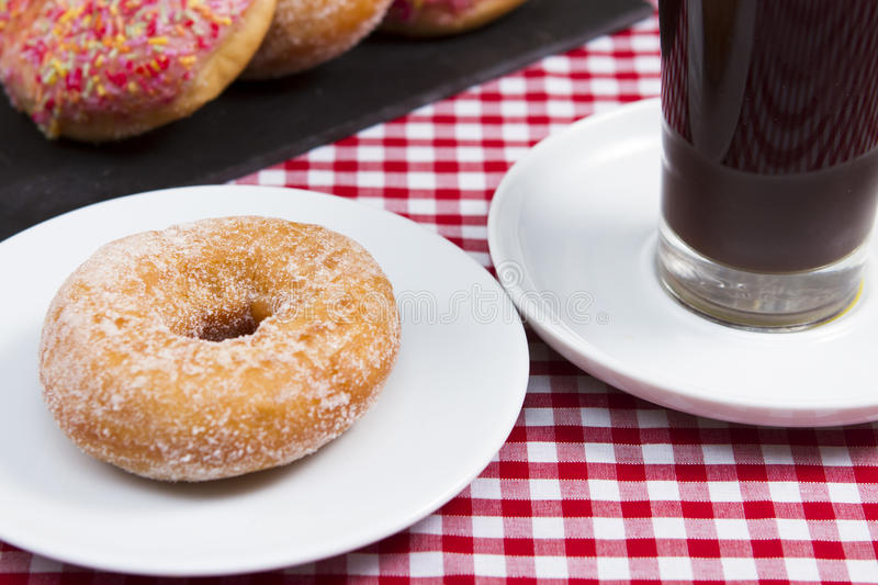 Donuts. A slate plate of assorted donuts with a cup of coffee stock image