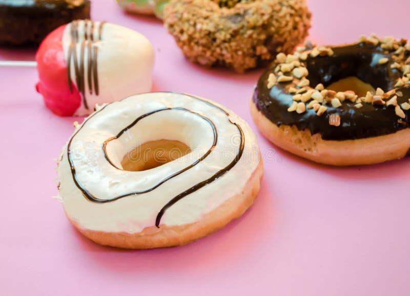 Donuts sorterade med glasat p? bl?tt och rosa royaltyfri foto