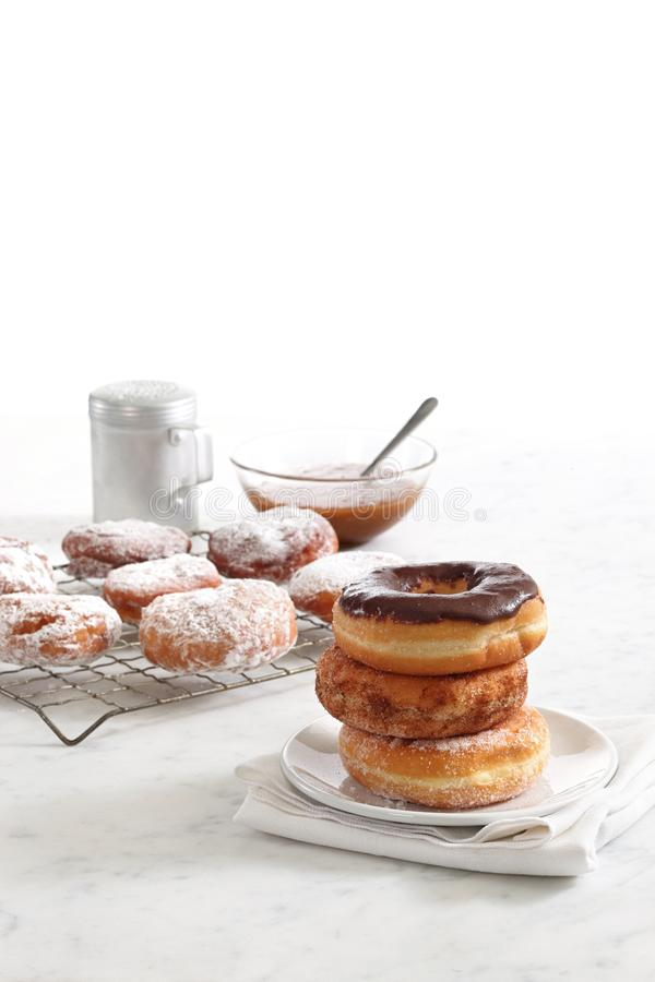 Donuts stacked on a plate. With freshly made donuts on tray in background royalty free stock photo