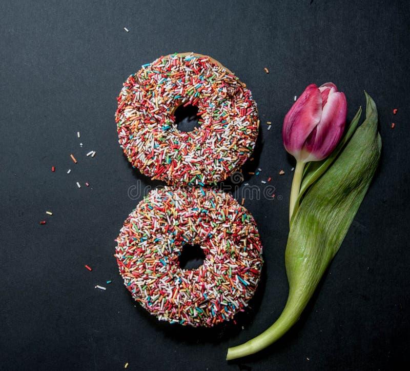 Donuts voor acht maart en bloem op zwarte achtergrond royalty-vrije stock fotografie