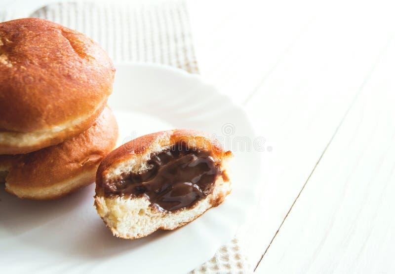 Donuts z czekoladowym plombowaniem na bielu talerzu, biała drewniana tło kopii przestrzeń zdjęcie stock