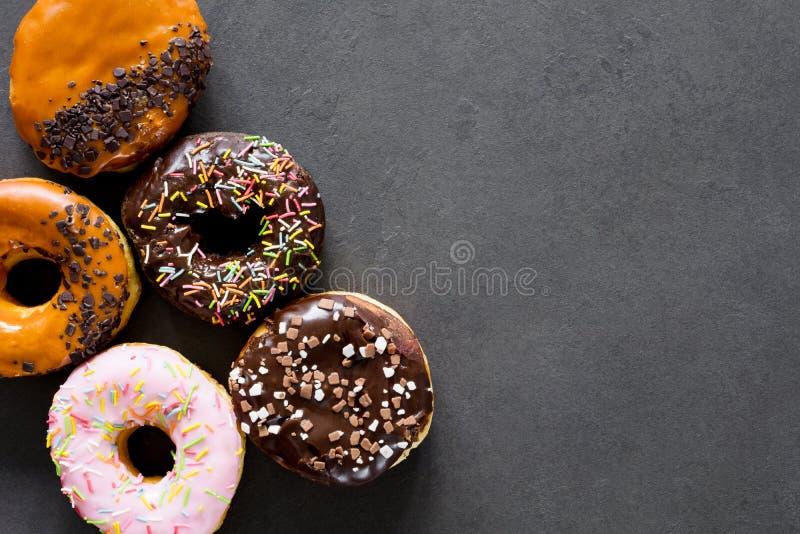 Donuts z glazerunkiem i confetti na kamienia stole zdjęcie stock
