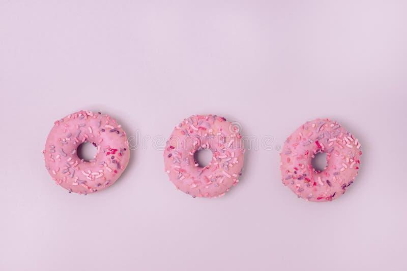 Donuts Z lodowaceniem na Pastelowych menchii tła Donuts kopii przestrzeni Odgórnego widoku Błękitnego Słodkiego Smakowitego miesz obrazy stock