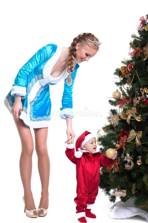A donzela alegre da mãe-neve mantém bebê-Santa Claus fotografia de stock
