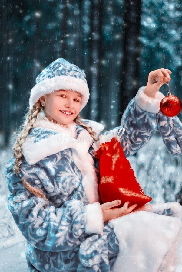 Donzela alegre no traje festivo a menina é de sorriso e guardando um brinquedo e um saco de ano novo com presentes floresta do in fotos de stock royalty free