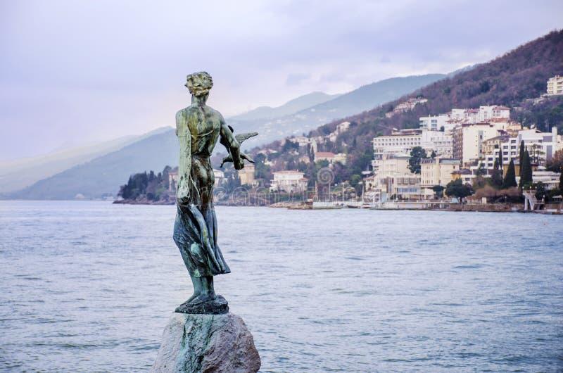 Donzela com a estátua da gaivota com o mar de adriático no fundo em Opatia, Croácia imagem de stock