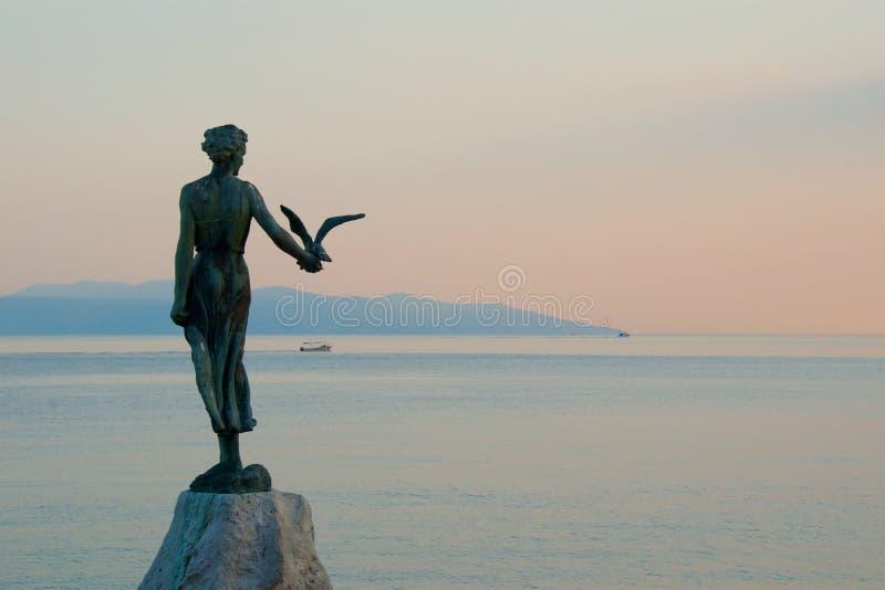 Donzela com a gaivota que está na rocha em Opatija, Croácia imagens de stock