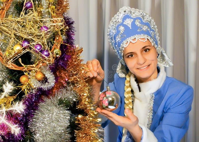 A donzela da neve decora uma árvore de Natal foto de stock royalty free