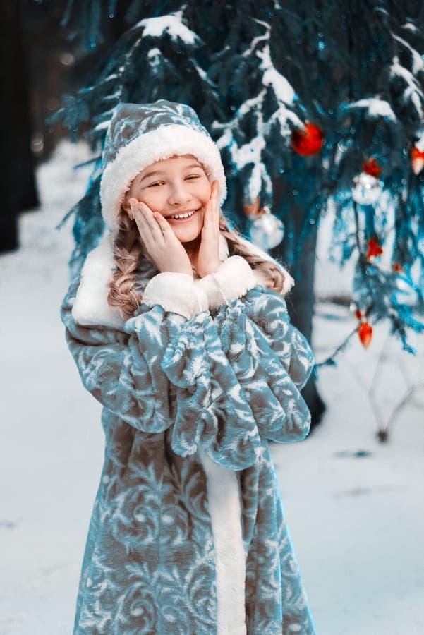 Donzela da neve a menina congelou-se no inverno no bebê da floresta aquece as mãos e a cara Ano novo feliz imagens de stock royalty free
