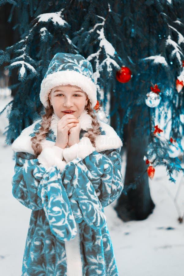 Donzela da neve a menina congelou-se no inverno na floresta que a criança aquece suas mãos Ano novo feliz toned fotos de stock