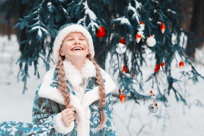 Donzela da neve a menina congelou-se no inverno na floresta que a criança aquece suas mãos Ano novo feliz toned imagem de stock royalty free