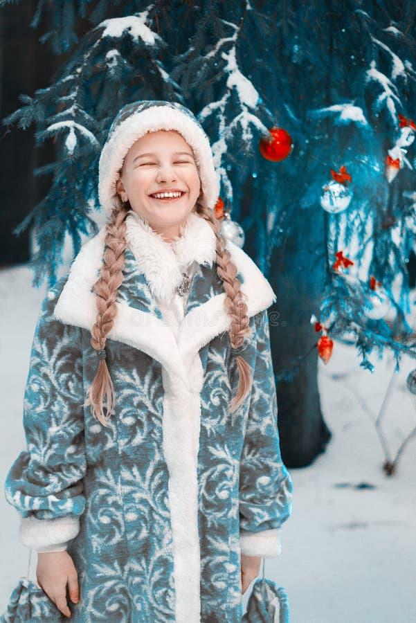 Donzela da neve a menina congelou-se no inverno na floresta que a criança aquece suas mãos Ano novo feliz toned imagens de stock