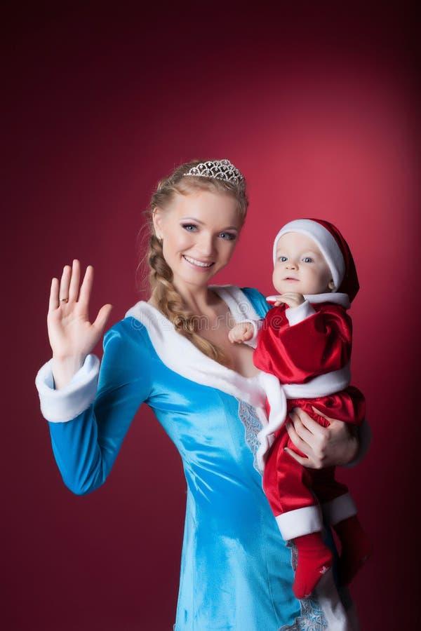 A donzela feliz da mamã-neve guarda bebê-Santa Claus fotos de stock