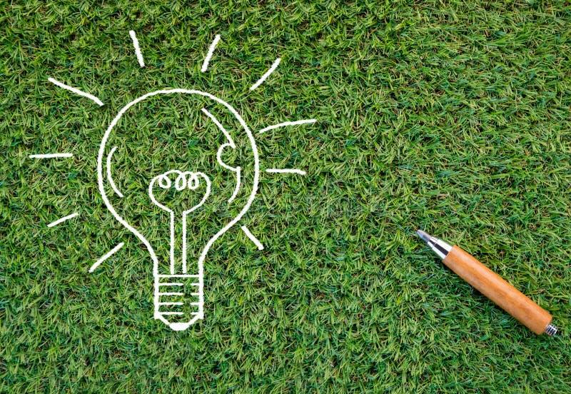 Doodle идеи света шарика на текстуре травы и деле карандашей стоковые изображения rf