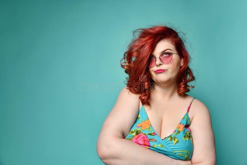Doof voor argumenten plus-grootte gelooft de te zware dame in zonnebril en sundress met haar gekruiste wapens niet op munt royalty-vrije stock fotografie