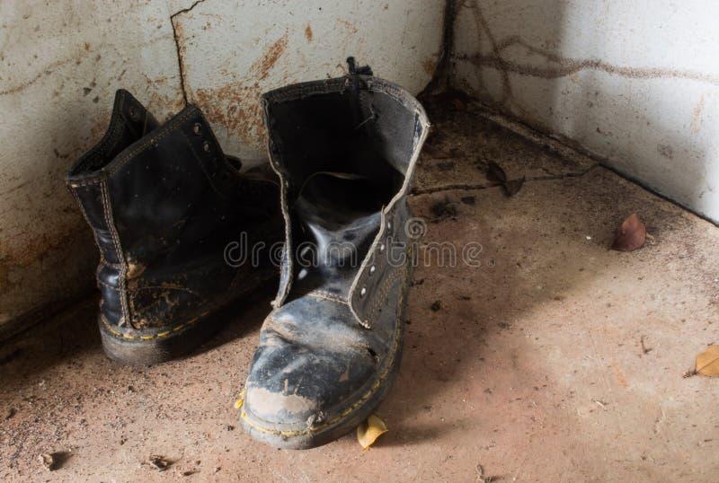 Doopvontmening van paar oude laarzen binnen een oud huis stock fotografie