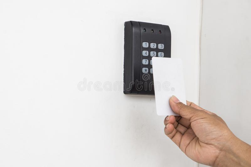 Door access control - young woman holding a key card to lock and unlock door., Keycard touch the security system to access the doo royalty free stock image