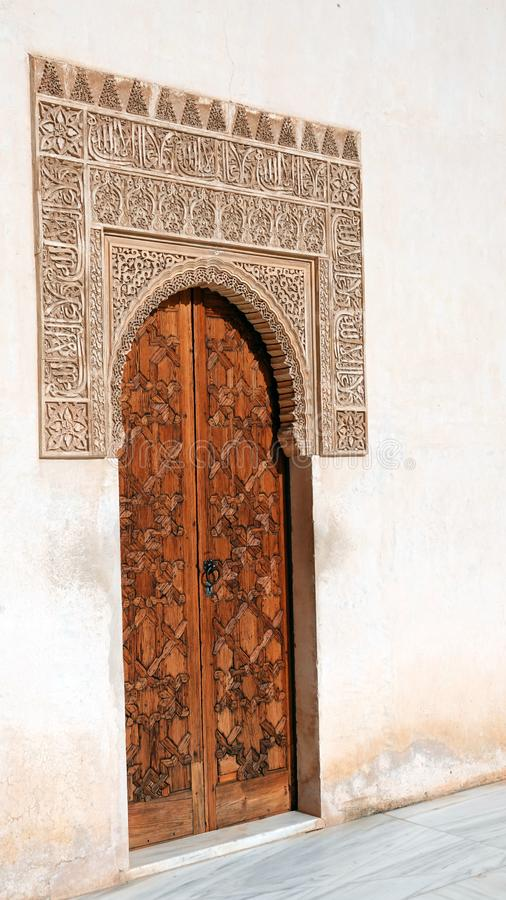 Door at Nasrid palace of the Alhambra in Granada, Andalusia. Door with arch decorations of arabesque ornaments stock images