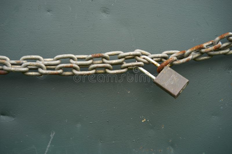Old rusty chain and pad lock. Door being secured with a rusty chain and pad lock royalty free stock photos