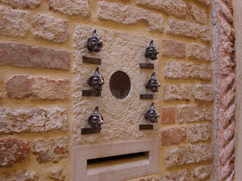 Door bell. Fun characters adorn the walls of this house and serves as doorbells. Venice, Italy stock photos