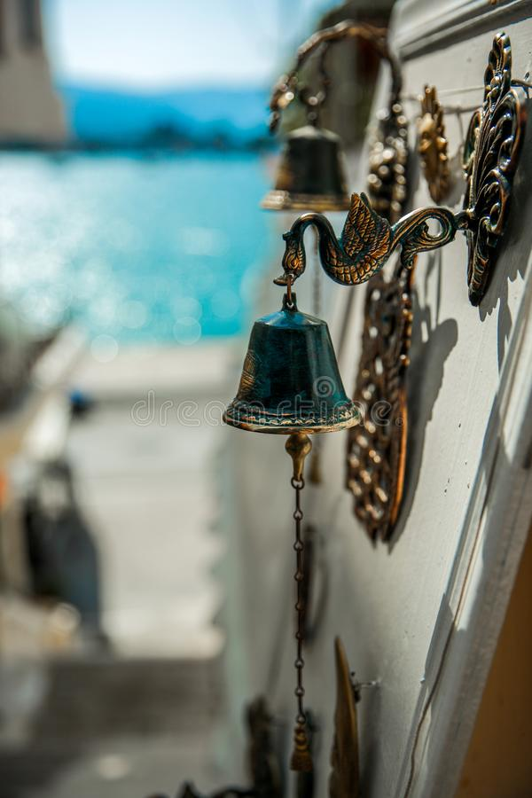 Door bells are sold on the streets of a small town on the island of Greece, the sea is in the background. Paros, Greece royalty free stock image