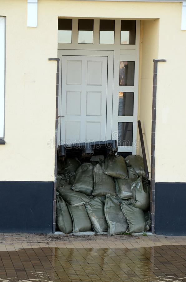 A door blocked with sandbags due to an approaching storm surge, the water stands close to the door. A door has been blocked with sandbags due to an approaching royalty free stock photo