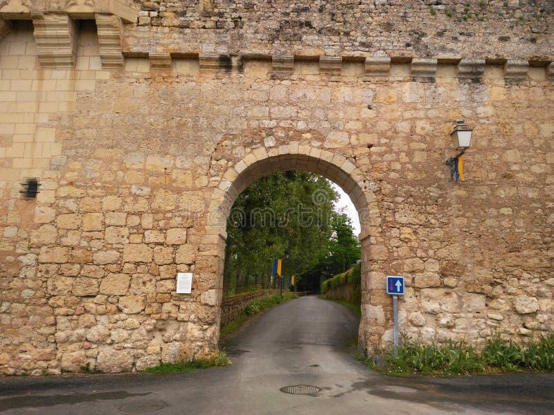 16th century construction. Door bridge lamp Road path Stone wall hole greenery green stock photography