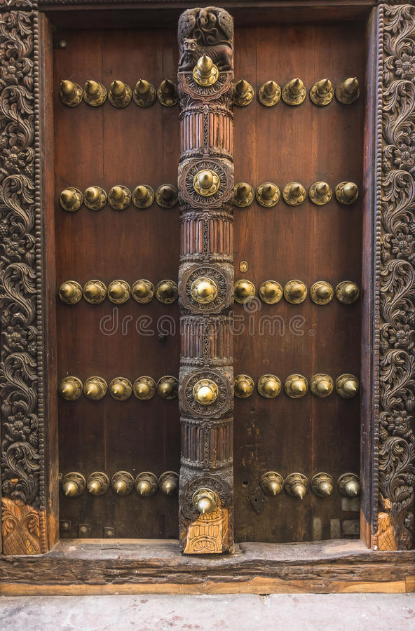 Door of building in Stone Town, Zanzibar. Old weathered carved traditional door of building in Stone Town, Zanzibar, Tanzania. Africa royalty free stock image
