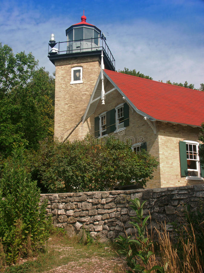Door County Lighthouse Cottage. Small, old stone home and lighthouse combined on the shores of Lake Michigan's Door County stock photo