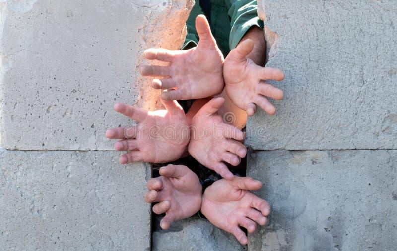 Door de gebroken blokken in de concrete muur uit uitgerekt de handen van vluchtelingenimmigranten die om water en voedsel vragen stock afbeelding