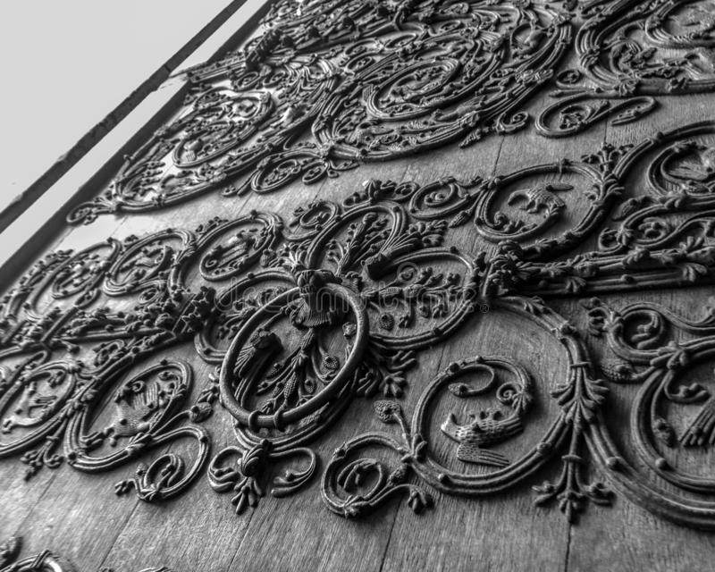 Door detail of Notre Dame de Paris Cathedral, Paris, France. Old wooden door with a metallic pattern close-up. The stock photography