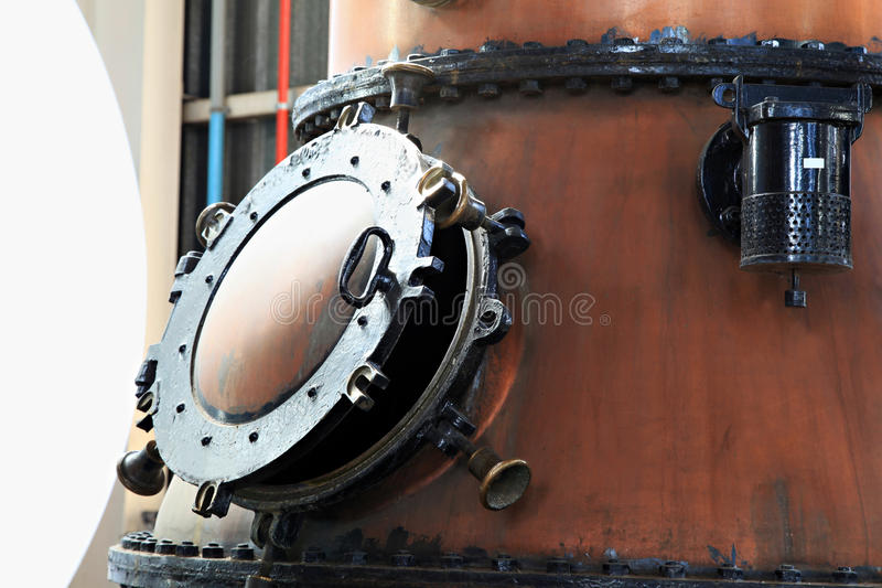 Door of a gin kettle. Door on old brass gin kettles in a distill stock photo