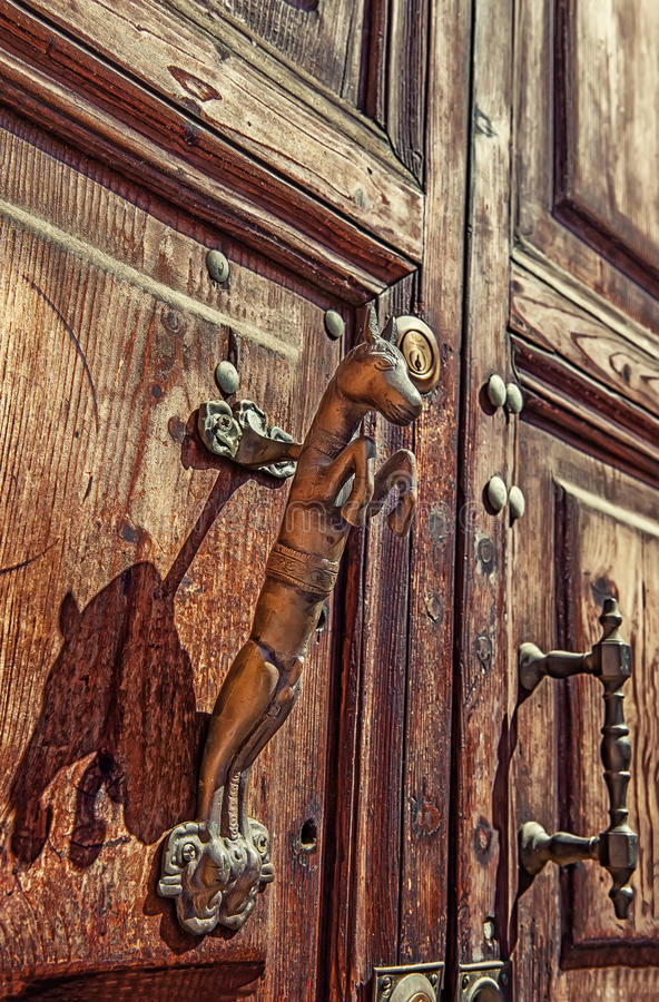 Door handle made of metal in the form of a rearing horse on old textured doors. The vertical frame stock photo