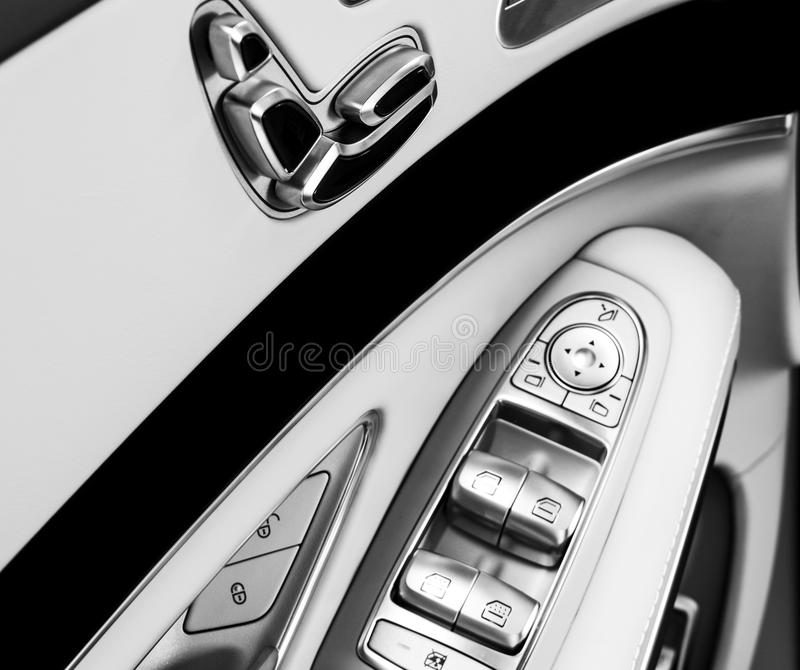 Door handle with Power seat control buttons of a luxury passenger car. White leather interior of the luxury modern car. Modern car. Interior details. Black and royalty free stock photos