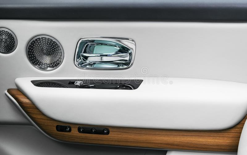Door handle with power window control buttons of a luxury passenger car. White perforated leather interior with stitching and natu. Ral wood panel. Modern car royalty free stock images