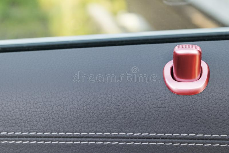 Door handle with red lock control buttons of a luxury passenger car. Black leather interior of the luxury modern car. Modern car. Interior details royalty free stock photo