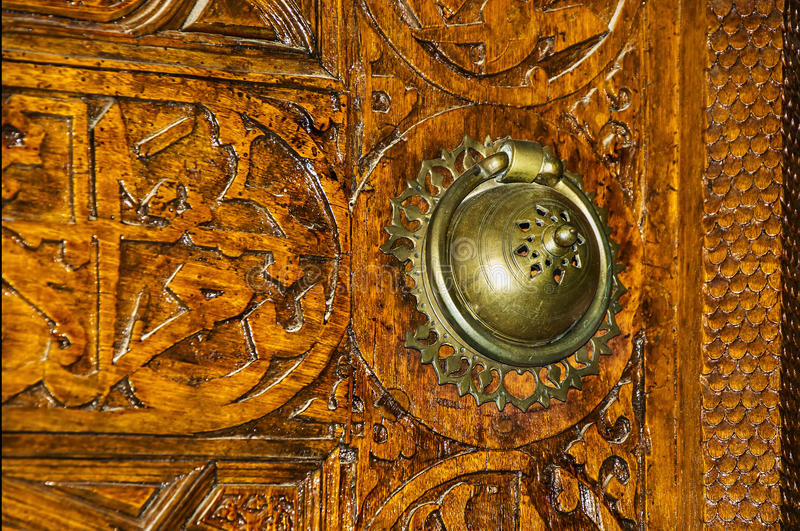 Door handle and wooden carvings stock photo